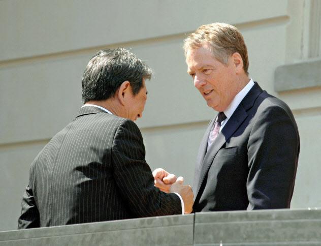 日米は8月中に再び閣僚協議を開く(1日、ワシントンで握手するライトハイザー氏(右)と茂木氏)=共同