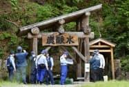 男女2人が倒れていた井戸の周辺を調べる福島県警の捜査員(15日午後、福島県金山町)=共同