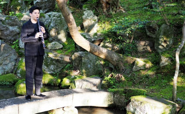 「ながらの座・座」の庭でクラリネットを奏でる吉田誠(大津市)