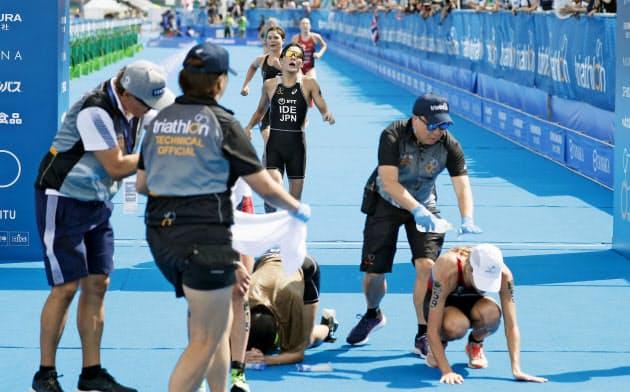 トライアスロンの東京五輪予選で、ゴール後に倒れ込む女子選手たち(東京・お台場海浜公園)=共同