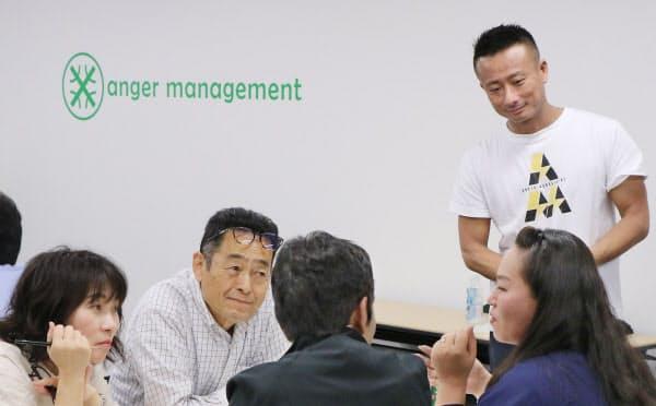 日本アンガーマネジメント協会が主催したセミナーでグループ討論する参加者。右奥は代表理事の安藤俊介さん(東京都港区)