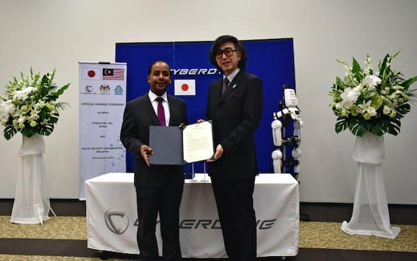 マレーシアのクラセガラン人的資源相(左)から支援表明書を受理するサイバーダインの山海嘉之社長(15日、茨城県つくば市)
