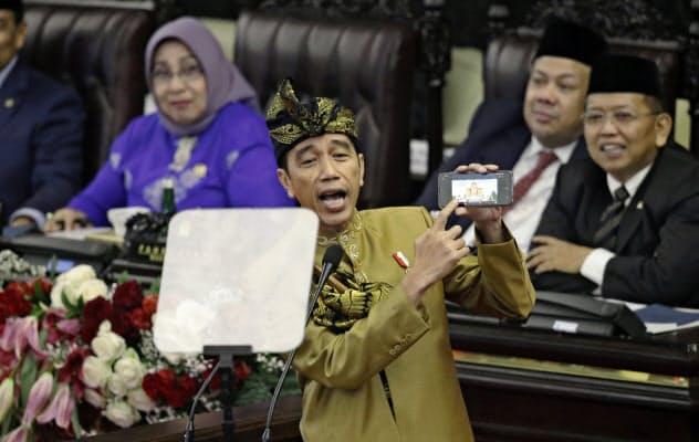 16日、スマートフォンを示しながら演説するインドネシアのジョコ大統領=AP