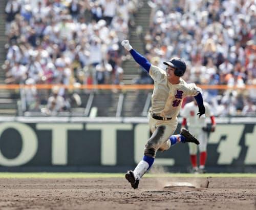 星稜―智弁和歌山 タイブレークの14回裏星稜1死一、二塁、左中間にサヨナラ3ランを放ち、ガッツポーズで二塁を回る福本(17日、甲子園)=共同