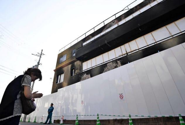 放火殺人事件が起きた「京都アニメーション」第1スタジオの前で手を合わせる女性(17日午後、京都市伏見区)=共同