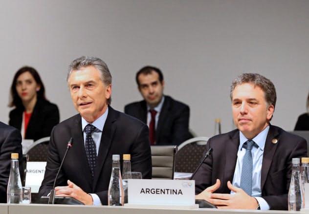 アルゼンチンのドゥホブネ財務相(右)はマクリ大統領の下でIMFとの交渉役などを務めた(2018年7月、ブエノスアイレス)=ロイター