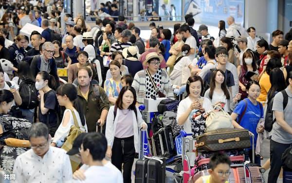 お盆休みを海外で過ごした人たちなどで混雑する成田空港の到着ロビー(18日午後)=共同