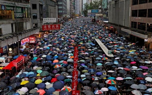 傘をさしながら行進するデモ参加者ら(18日、香港)=ロイター