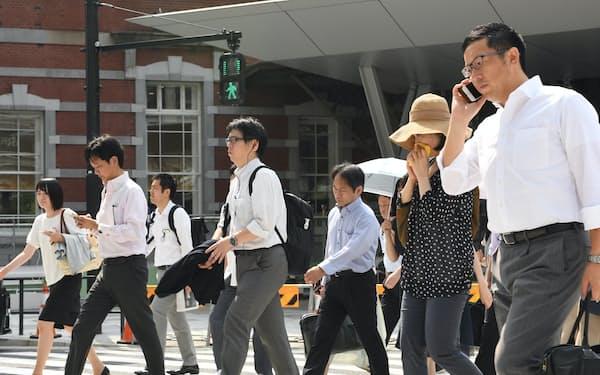 強い日差しの中を歩く人たち(東京都千代田区)