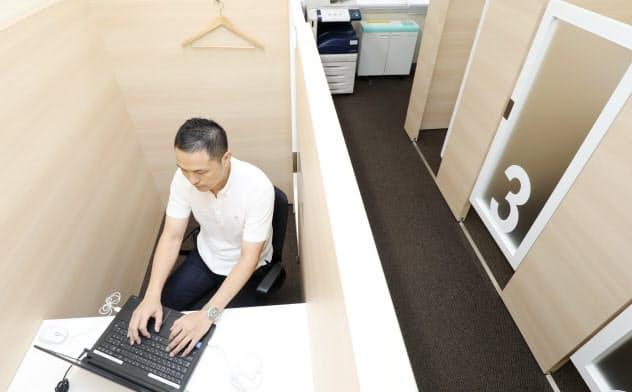 サテライトオフィスで働く竹内さん。仕事場は個人のブースになっている