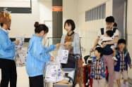 韓国語のパンフレットやお菓子が入った袋を手渡した(19日、新千歳空港)