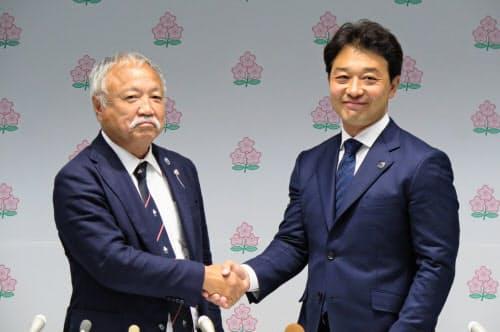 就任記者会見後、握手を交わす日本ラグビー協会の森重隆会長(左)と岩渕健輔専務理事(6月29日)