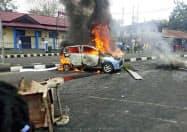 19日、インドネシア東部ニューギニア(パプア)島での暴動で炎上する自動車=AP