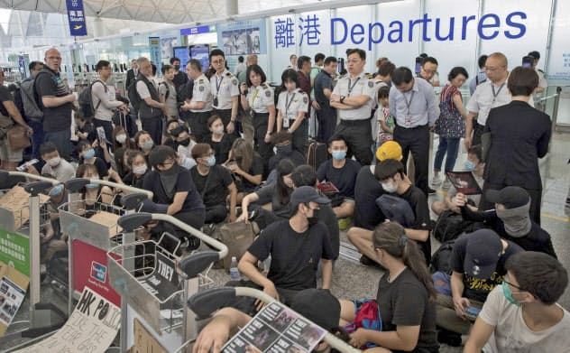 香港国際空港では抗議活動の影響で9~13日に計約1000便が欠航した(13日、空港で座り込む抗議者を見張る保安担当者)=AP