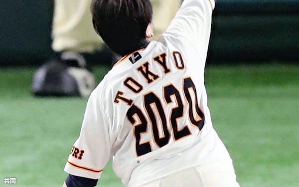 背番号「2020」のユニホームを着用して始球式を務める東京都の小池百合子知事(11日、東京ドーム)=共同