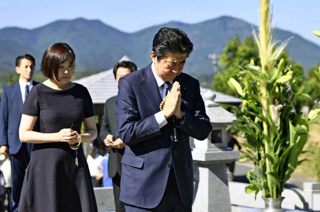 父の晋太郎元外相の墓前で手を合わせる首相。左は昭恵夫人(13日、山口県長門市)