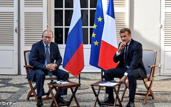 19日、会談前に取材に応じるマクロン仏大統領(右)とロシアのプーチン大統領(仏南部)=ロイター