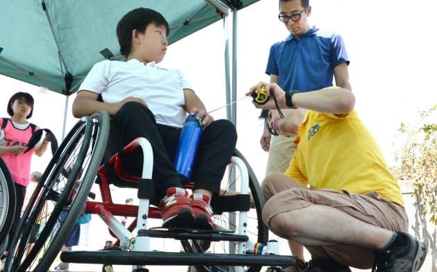 車いすテニス大会の会場で車いすを整備するオーエックスエンジニアリングの担当者(3日、仙台市)