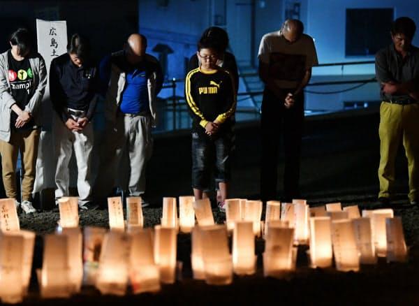 被災地に並ぶ灯籠の前で、犠牲者の冥福を祈り黙とうする人たち(20日未明、広島市安佐南区)