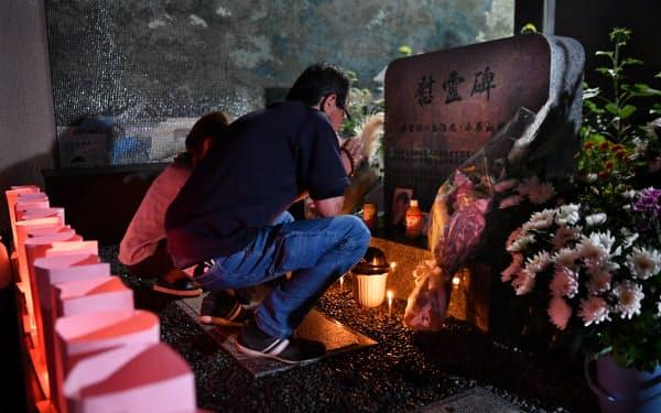 犠牲者の冥福を祈り、慰霊碑の前で手を合わせる人たち(20日未明、広島市安佐南区)