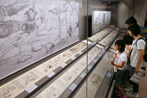 地元に実在した稲生平太郎に起こった怪異を描いた稲生物怪録(いのうもののけろく)絵巻を見る人たち(広島県三次市の三次もののけミュージアム)