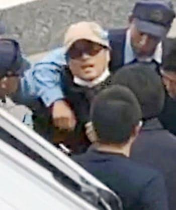 大阪市東住吉区の路上で、茨城県警の捜査員らに確保される宮崎文夫容疑者(18日、近隣住民提供)=共同