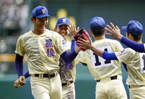決勝進出を決め、笑顔でタッチを交わす奥川(左端)ら星稜ナイン(20日、甲子園)=共同