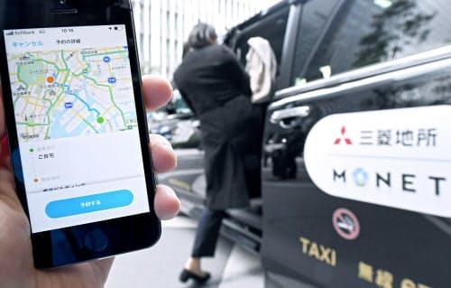 三菱地所とモネ・テクノロジーズが実施する、相乗りタクシーの実証実験。アプリで予約する(25日午前、東京都千代田区)