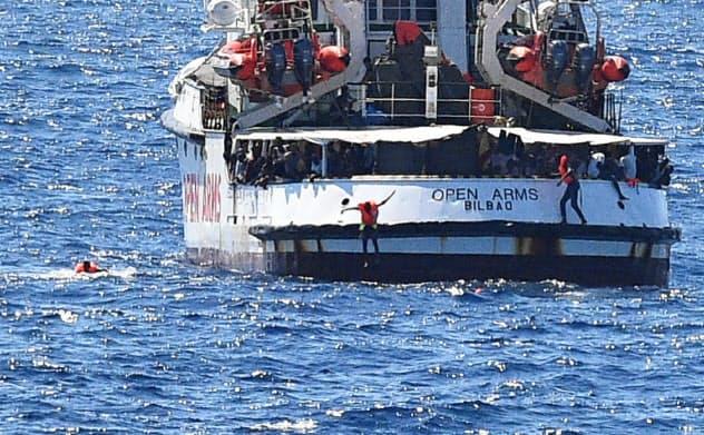 20日、スペインの救助船からイタリアのランペドゥーサ島沖で海に飛び込む移民たち=ロイター