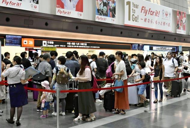 お盆休みを迎え、帰省客などで混雑する羽田空港国内線の出発ロビー(10日)=共同