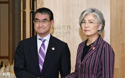 会談を前に握手する河野外相(左)と韓国の康京和外相=21日、北京郊外(共同)