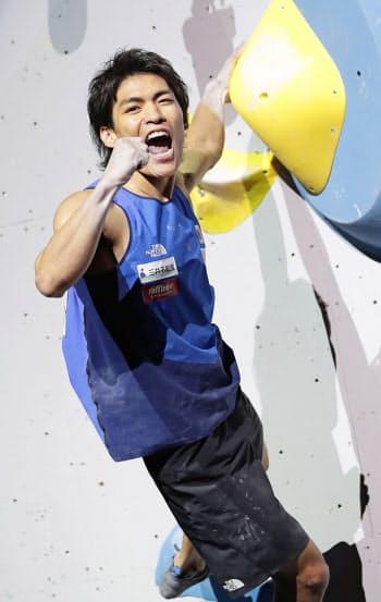 スポーツクライミング世界選手権の男子複合決勝で、ボルダリングの課題を完登しガッツポーズする楢崎智亜。金メダルを獲得し東京五輪代表に決まった(21日、東京都八王子市のエスフォルタアリーナ八王子)=共同