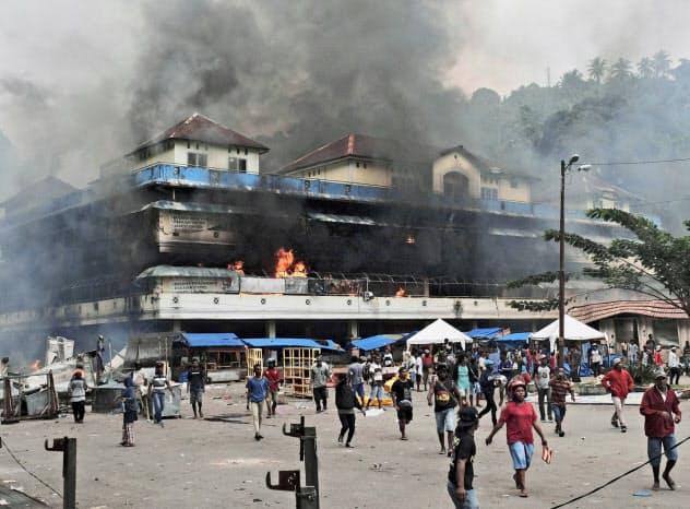 21日、インドネシア東部パプア州で暴動で燃やされた市場=AP