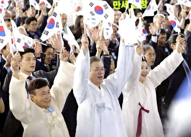 15日、韓国の天安で開かれた「光復節」の式典で万歳する韓国の文在寅大統領(手前中央)ら(聯合=共同)