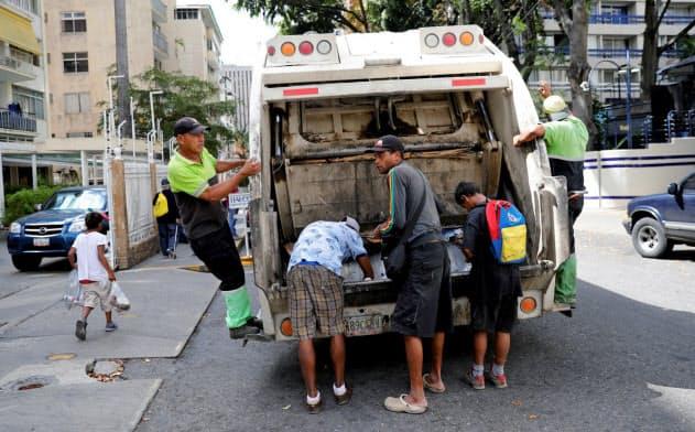 ゴミ収集車から食料をあさるベネズエラの子供(カラカスで)=ロイター