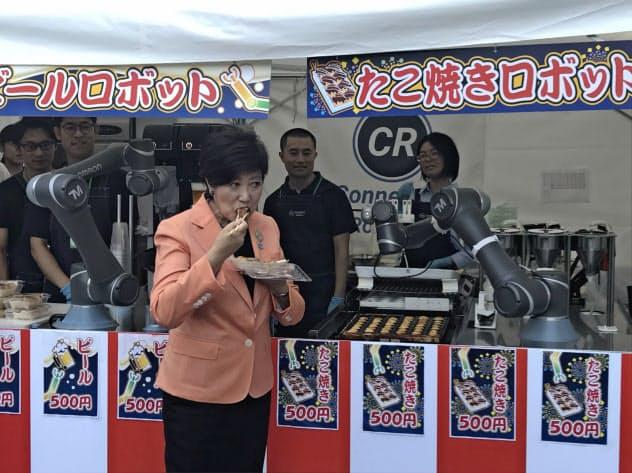 ロボットが調理したたこ焼きに舌鼓を打つ小池知事(22日、東京都港区)