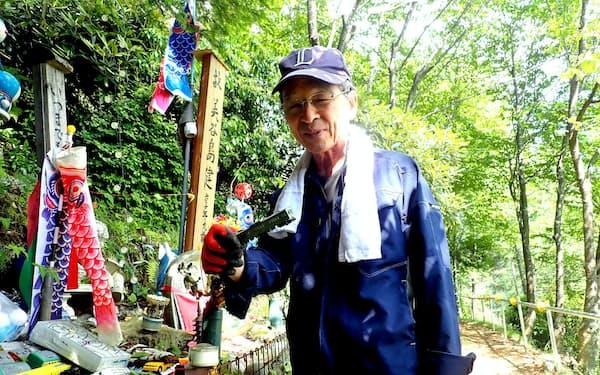 息子健ちゃんが好きだった鉄道の模型を手にほほ笑む美谷島さん(群馬県上野村)