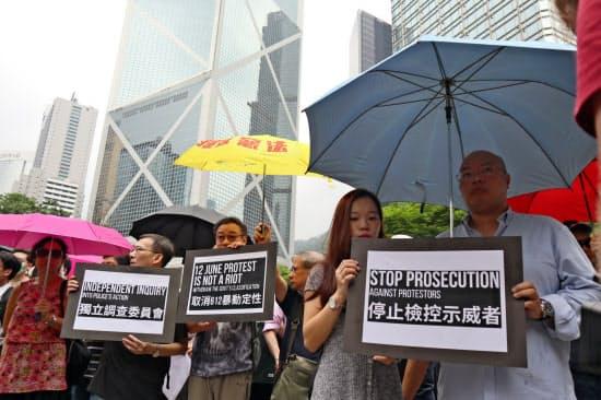 23日、会計事務所の従業員らが香港島中心部でデモ行進した