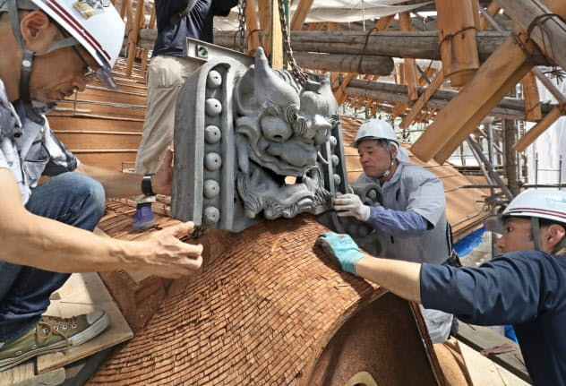 檜皮葺職人と瓦職人が協力し、清水寺本堂の屋根に鬼瓦を据え付ける=松浦弘昌撮影