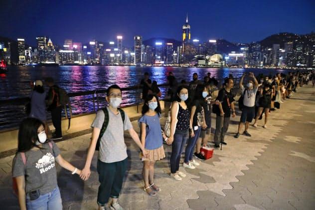 手をつなぎ、抗議の意志を示す「人間の鎖」を作るデモ参加者(23日、香港)=AP