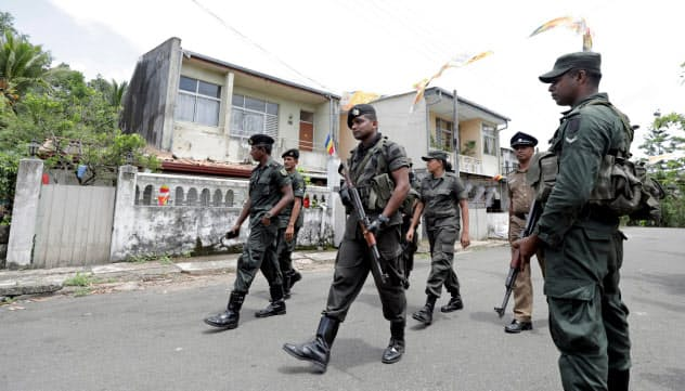非常事態宣言のもと、コロンボ近郊で警戒するスリランカ軍の兵士(5月)=ロイター