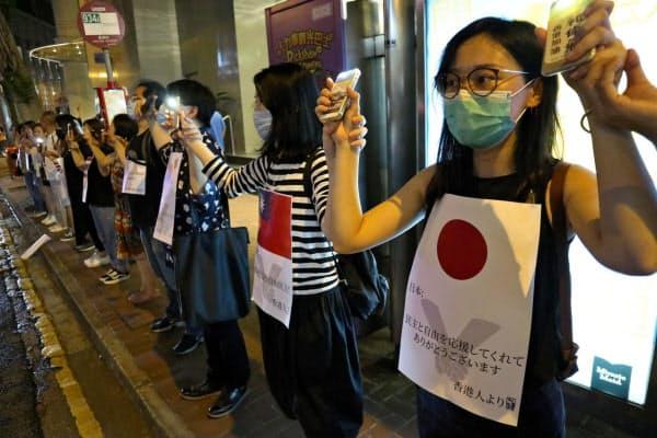 「人間の鎖」の参加者はデモへの支援に感謝するプラカードを掲げた(23日夜、香港)