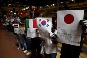 プラカードには日本語で「ありがとうございます」の言葉も(23日夜、香港)