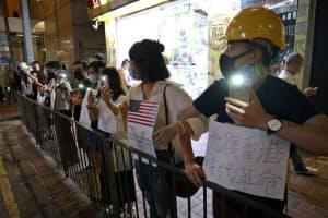 「人間の鎖」で抗議の意思を示した(23日夜、香港)