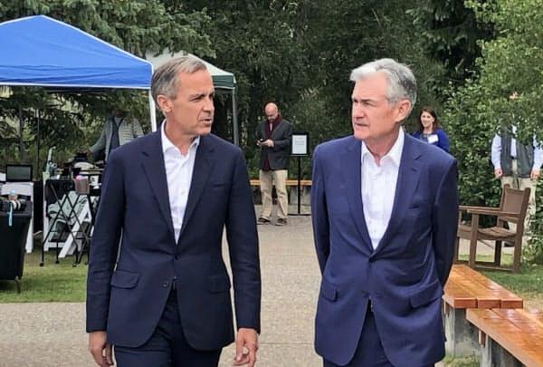 講演を終えたパウエルFRB議長(右)とカーニー・イングランド銀総裁(23日、米ジャクソンホール)