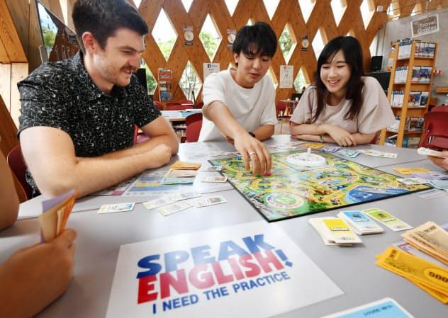 外国人スタッフ(左)とボードゲームを通じて英語を学ぶ学生(大阪府東大阪市の近畿大)