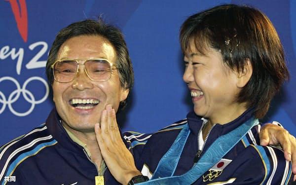 2000年9月、シドニー五輪マラソン女王の高橋尚子さんに、ひげをそった頬を触られて笑う小出義雄さん=共同