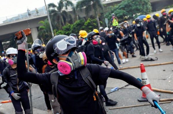 重装備のデモ参加者が警官にレンガを投げつけた(24日、香港)=ロイター
