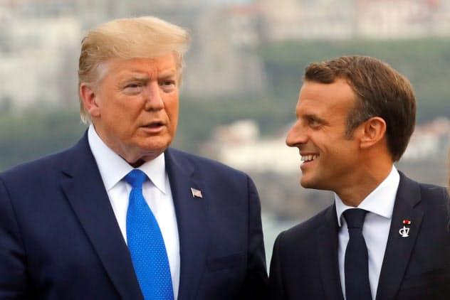 トランプ米大統領(左)を迎えるフランスのマクロン大統領(24日)=ロイター