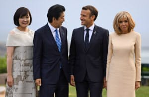 フランスのマクロン大統領(右から2人目)夫妻に迎えられる安倍首相夫妻(24日)=ロイター